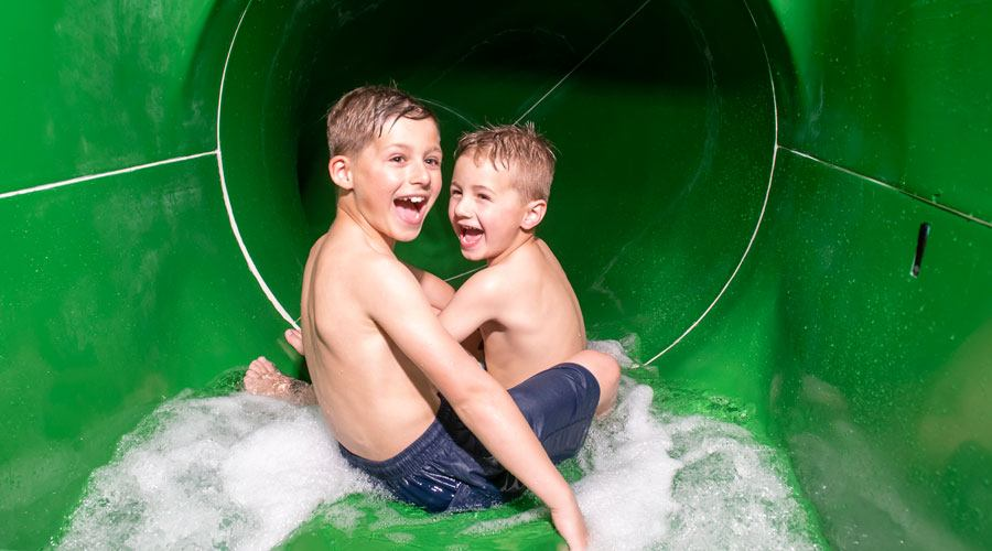 Two boys riding a flume at Twitchen House