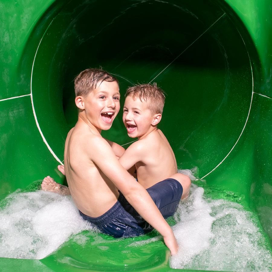Two boys riding the waterslide at Twitchen House